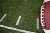 stock photo of football field  - A photo of an American Football field yardage markings with a football on the right border - JPG