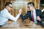 Two Businessman Expressed A Serious Expression And Fighting By Used Arm Wrestling On Wood Table. Con poster