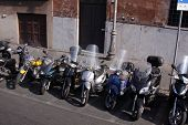 stock photo of vespa  - A line of parked motor bikes in Rome Italy - JPG