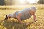 Exercise, Fitness, Age And Workout Concept. Healthy Sporty Mature Male Has Physical Exercises Outdoo poster
