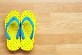 Yellow And Blue Sandals On Wooden Background poster