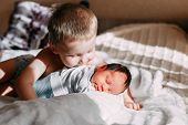 Elder Brother Kissing Newborn Baby Sister poster