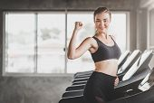 Healthy Caucasian Woman Show Her Bicep While Using Running Treadmill In Gym. Fitness Concept poster