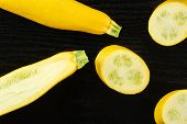 Group Of One Whole One Half Three Slices Of Raw Yellow Zucchini Flatlay On Black Wood poster