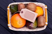 Assortment Of Fruits In Basket And Label. Assorted Tropical Fruits In Wicker Basket And Blank Cardbo poster