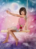 stock photo of fairy-tale  - Little girl sitting on the swing - JPG