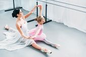 High Angle View Of Adorable Child In Pink Tutu Exercising With Teacher In Ballet School poster