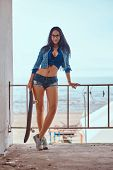 Smiling Seductive Hot Brunette Girl Wearing Short Shorts And Jeans Jacket Holds A Skateboard While S poster