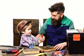 Son In Protective Helmet Learning To Use Screwdriver With Dad. Teamwork In Workshop Concept. Father  poster