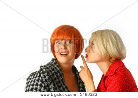 Two Happy Young Women Whispering And Surprised