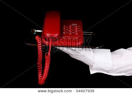 Mano en guante con bandeja de plata con teléfono aislada en negro