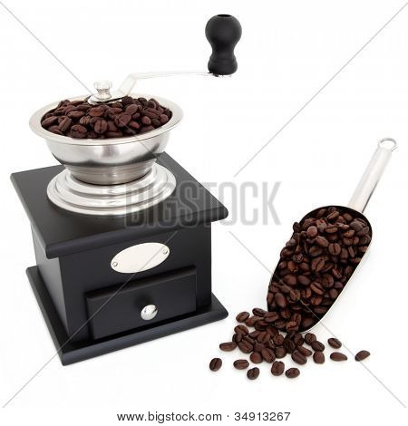 Manual retro coffee grinder with beans and in a metal measuring scoop over white background.