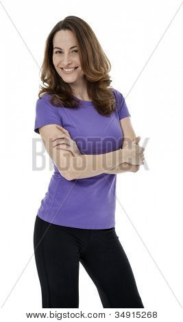 Forty year old woman standing with arms crossed on white background.
