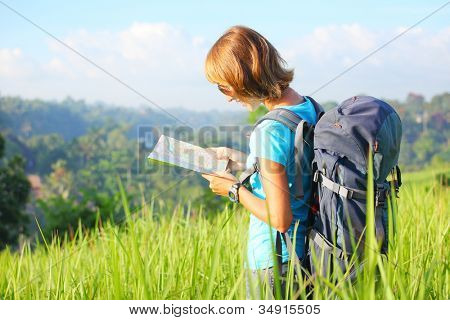 Young backpacker standing on a green meadow at sunny day and looking into a map