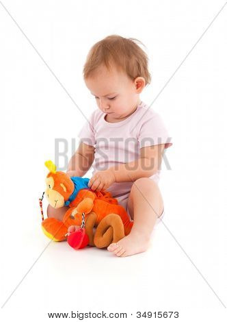 Cute baby girl lost in playing with soft toy.