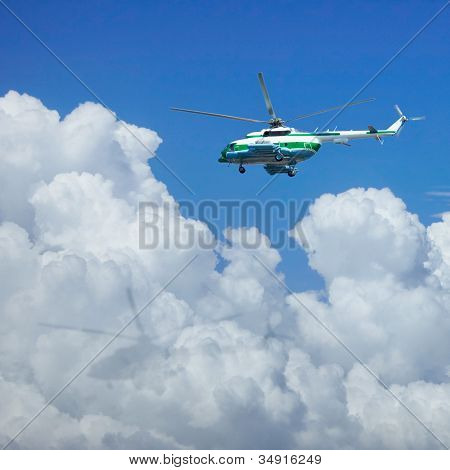 Helicopter Flying Above The Clouds