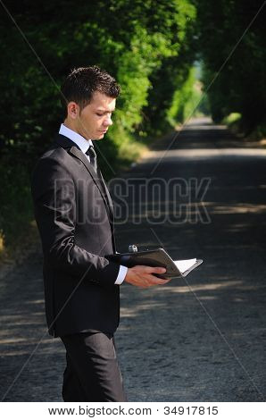 Business man read on road