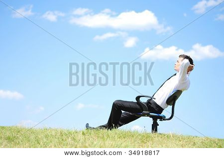 Business man relaxing on chair in nature