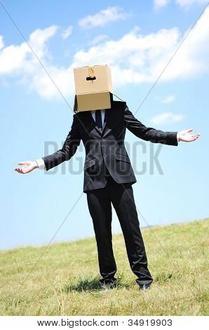 Business man with box on head in nature