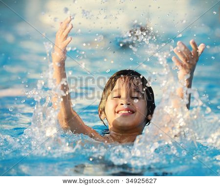 Kid splashing on summer pool