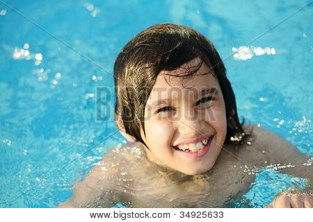 Little happy boy on pool