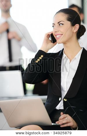 Successful businesswoman speaking on phone at office