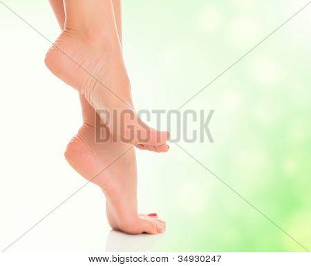 female feet on blurred green background