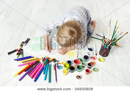 Child Drawing Picture With Crayon  In Album Using A Lot Of Painting Tools