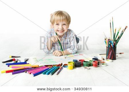 Happy Cheerful Child Drawing With Brush In Album Using A Lot Of Painting Tools