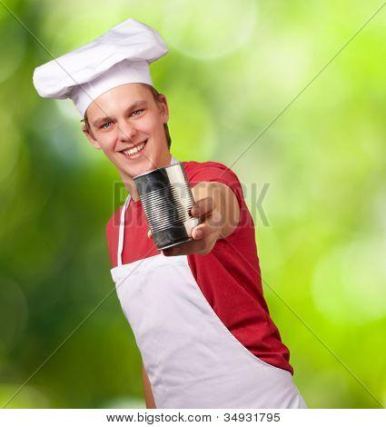 Porträt eines jungen Koch-Mannes hält eine Metall Blechdose vor einem Natur-Hintergrund