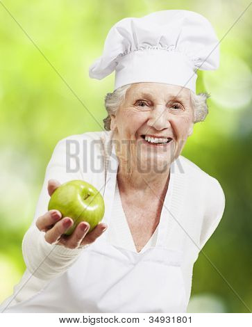 senior woman cook offering a green apple against a nature background