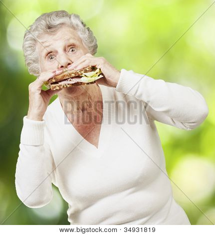 senior woman eating a healthy sandwich against a nature background