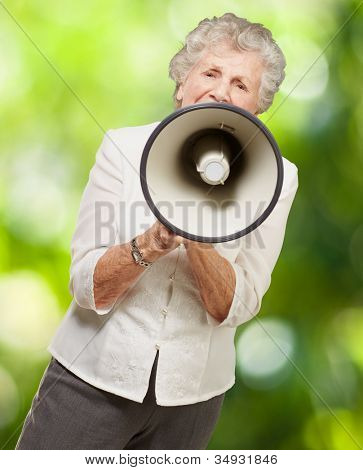 portrait of a senior woman screaming with a megaphone against a nature background