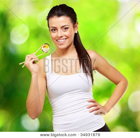 young woman holding a piece of sushi with chopsticks against a nature background