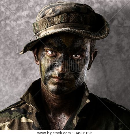 portrait of a young soldier face painted with a jungle camouflage against a grunge wall