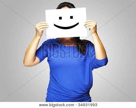 Woman showing a happy emoticon in front of face over a grey background