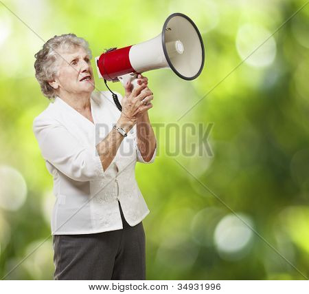 portrait of a senior woman holding a megaphone over a nature background