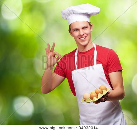 portrait of a young cook man holding an egg box and doing a good gesture over a nature background