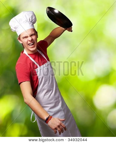 portrait of an angry young cook man hitting with a pan against a nature background