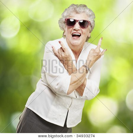 portrait of a senior woman doing a rock symbol against a nature background