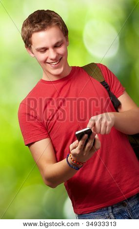 portrait of a young man touching a mobile screen against a nature background