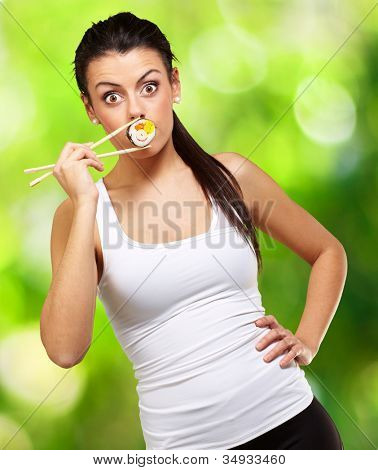 young woman covering her mouth with a sushi piece against a nature background