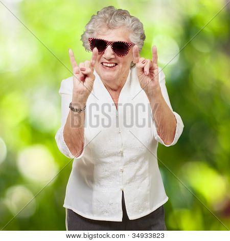 portrait of a happy senior woman doing a rock symbol against a nature background