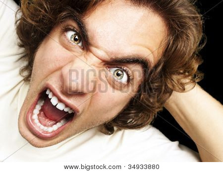 portrait of a furious young man shouting against a black background
