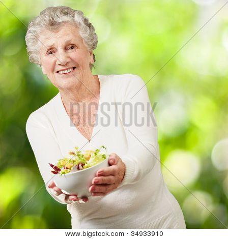 Retrato de una mujer mayor con una ensalada fresca sobre un fondo de naturaleza