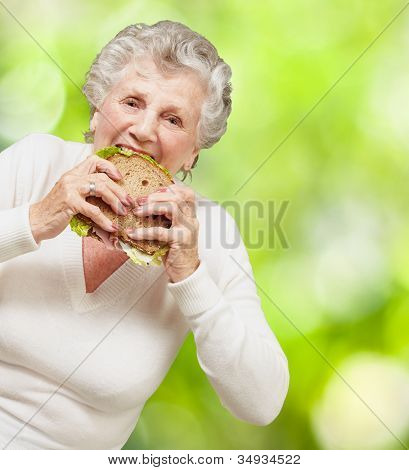 portrait of a senior woman eating a vegetable sandwich against a nature background