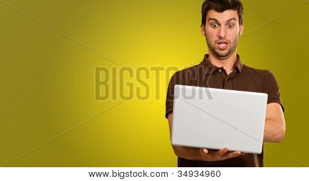 Young Man Using Laptop Isolated On Yellow Background