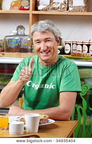 Elderly happy man in organic caf�© holding his thumbs up