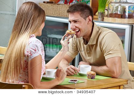 Young woman letting man taste a muffin in a caf�©
