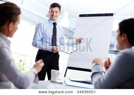 Cheerful office worker pointing at the blank whiteboard making a presentation